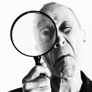 Monochrome portrait of senior man peering through magnifying glass, grimacing