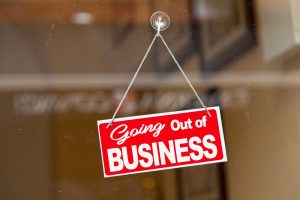 "Red sign hanging at the glass door of a shop saying: ""Going out of business""."