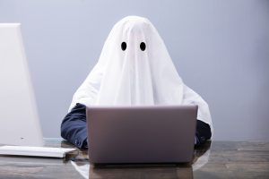 Suited person with ghost sheet on
