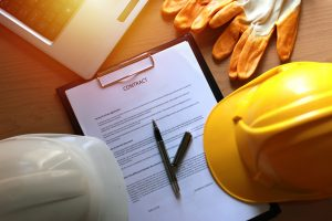 overhead image of a contract on a clipboard, construction helmet, gloves, edge of laptop