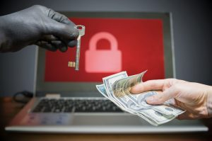 Hand representing hacker offering old-time key to another hand with cash, with a laptop in background with red screen and lock icon